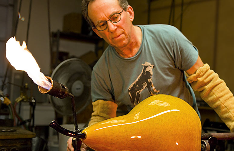 Glass artist Michael Cohn finishes blowing a giant glass pear